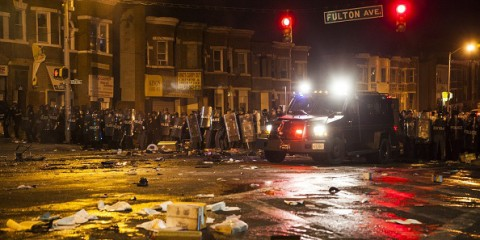 WASHINGTON, USA - APRIL 27: Police retreat from the hulks of burned out cars in the middle of an intersection during riots in Baltimore, USA on April 27, 2015. Protests following the death of Freddie Gray from injuries suffered while in police custody have turned violent with people throwing debris at police and media and burning cars and businesses. (Photo by Samuel Corum/Anadolu Agency/Getty Images)