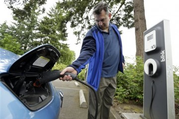 Patrick Conner' shows how to plug his Nissan Leaf electric car at a charging station at the public library in Hillsboro, Ore., Tuesday, May 19, 2015.    Fuel-efficient, hybrid and electric cars are a boon for the environment, but their growing popularity means shrinking fuel tax revenues for state coffers and less money to pay for road and bridge projects. Oregon is about to embark on a first-in-the-nation program that aims to address this shortfall by testing the feasibility of taxing motorists not for the fuel they use, but for the miles they drive.  (AP Photo/Don Ryan)
