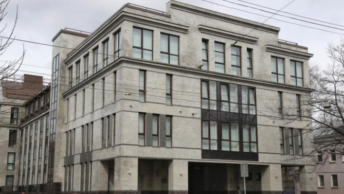 """In this picture taken on Sunday, April 19, 2015,  a women enters the four-story building known as the """"troll factory""""  in St. Petersburg, Russia. The """"troll factory"""" is where hundreds of young Russians work around the clock writing blogs and posting comments on the Internet staunchly supporting President Vladimir Putin and attacking the West. (AP Photo/Dmitry Lovetsky)"""
