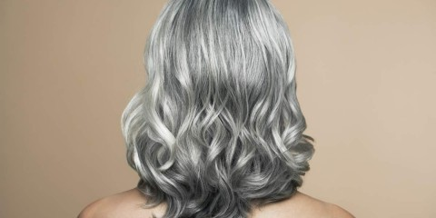 Nude mature woman with grey hair, back view.