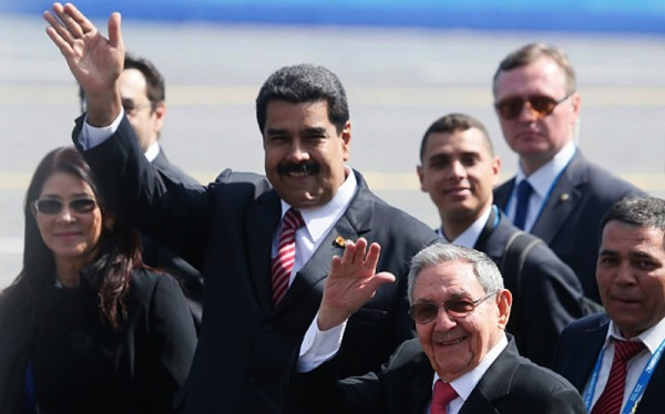 Venezuelan President Nicolas Maduro, centre, and Cuban President Raul Castro, centre right, after the parade (EPA)