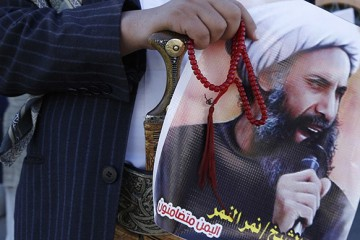 "A Shi'ite protester carries a poster of Sheikh Nimr al-Nimr during a demonstration outside the Saudi embassy in Sanaa October 18, 2014. The Shi'ite Muslim minority in Saudi Arabia's Eastern Province have long felt marginalised by the Sunni ruling dynasty, and protests for greater rights as part of the 2011 Arab Spring brought a crackdown on both protesters and demands for reform. But now, death sentences for three Shi'ite Muslims, including prominent dissident cleric Nimr, suggest that the region's wider turmoil is further hardening attitudes toward the sect at home. The poster reads: ""We all are Sheikh Nimr al Nimr."" Picture taken October 18, 2014. REUTERS/Khaled Abdullah (YEMEN - Tags: POLITICS CIVIL UNREST RELIGION) - RTR4BEXA"