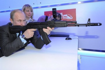 epa03197062 Russian Prime Minister and president-elect Vladimir Putin aims with an AK-47 submachine-gun mock-up in the electronic shooting gallery while visiting the Russian Railways Company's Research and Technological Center in Moscow, Russia 26 April 2012. Inauguration of Vladimir Putin as president of Russia is scheduled on 07 May 2012.  EPA/ALEXEY DRUGINYN / RIA NOVOSTI / GOVERNMENT PRESS SERVICE POOL MANDATORY CREDIT