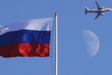 A plane flies over the Russian flag atop the Konstantin Palace in St.Petersburg, Russia, Friday, July 24, 2015.  Friday marks the eve of the Preliminary draw for the 2018 World Cup in Russia. (AP Photo/Dmitry Lovetsky)