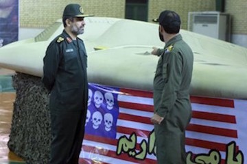 FILE - This file photo released on Thursday, Dec. 8, 2011, by the Iranian Revolutionary Guards, claims to show the chief of the aerospace division of Iran's Revolutionary Guards, Gen. Amir Ali Hajizadeh, left, listening to an unidentified colonel as he points to US RQ-170 Sentinel drone which Tehran says its forces downed earlier this week. (AP Photo/Sepahnews, File) EDS NOTE: THE ASSOCIATED PRESS HAS NO WAY OF INDEPENDENTLY VERIFYING THE CONTENT, LOCATION OR DATE OF THIS IMAGE.