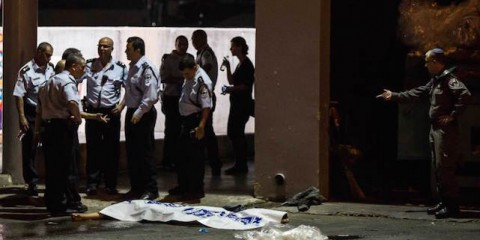 Israeli police stand by the shrouded body of Palestinian attacker in Beersheba, Israel, Sunday, Oct. 18, 2015. An Arab attacker armed with a gun and a knife opened fire in a southern Israel bus station on Sunday, police said, killing an Israeli soldier and wounding 10 people in one of the boldest attacks yet in a month long wave of violence. (AP Photo/Tsafrir Abayov)