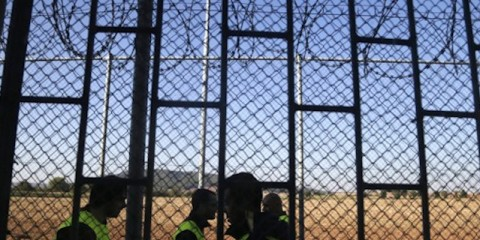Guards walk past a razor wire fence securing a former prison in Drahonice, Czech Republic, Friday, Oct. 2, 2015. Anticipating a possible influx of migrants in the country, the Czech Republic is turning the prison into a new detention center for up to 240 of them. (AP Photo/Petr David Josek)