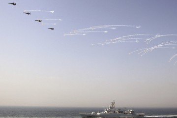 Chinese jet fighters release flares as they fly over a Chinese vessel during the fleet's review of the China-Russia joint naval exercise in the Yellow Sea April 26, 2012. Chinese and Russian  warships concluded a live ammunition exercise on Thursday, following a no-weapon joint war game earlier the same day, Xinhua News Agency reported. REUTERS/China Daily (CHINA - Tags: MILITARY POLITICS TPX IMAGES OF THE DAY) CHINA OUT. NO COMMERCIAL OR EDITORIAL SALES IN CHINA - RTR3192K