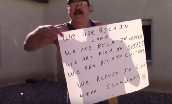 "Former Costilla County Sheriff holds a sign called new residents ""scumbags."""
