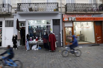 Boys ride on their bicycles past shops in the neighbourhood of Molenbeek, where Belgian police staged a raid following the attacks in Paris, at Brussels, Belgium November 15, 2015. Belgian authorities say two of the gunmen who staged the deadly assaults on Paris on Friday were from the capital Brussels, and its poorer municipality of Molenbeek. Police detained several people in the mainly Muslim neighbourhood, and brought a bomb disposal van to the area. REUTERS/Yves Herman  - RTS76OK