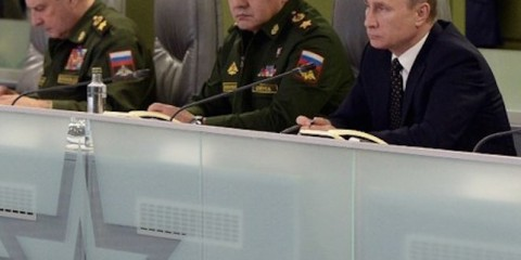 """Russian President Vladimir Putin (R), accompanied by Defence Minister Sergei Shoigu (C), meets with top military officials at the National Defence Control Centre of the Russian Federation in Moscow on November 17, 2015. President Vladimir Putin on November 17 ordered the Russian navy in the Mediterranean to establish contact with its French counterparts and work together """"as allies"""" in a campaign against the Islamic State group in Syria. AFP PHOTO / SPUTNIK / ALEXEI NIKOLSKY / AFP / SPUTNIK / ALEXEI NIKOLSKY"""