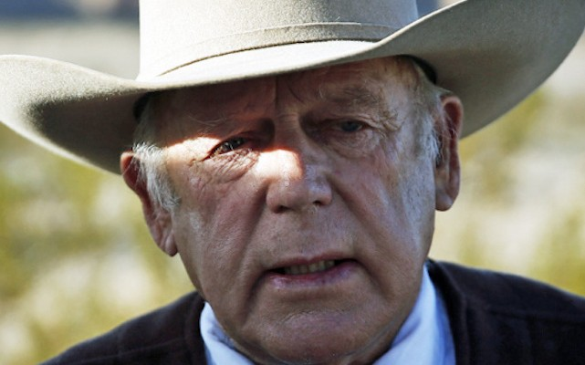 Rancher Cliven Bundy speaks to media while standing along the road near his ranch Wednesday, Jan. 27, 2016, in Bunkerville, Nev. Cliven Bundy and his wife Carol Bundy was returning from a trip to visit the family of LaVoy Finicum, a 55-year-old rancher from Cain Beds, Ariz., who died Tuesday after law enforcement officers initiated a traffic stop near the Malheur National Wildlife Refuge. It's unclear what happened in the moments before his death. (AP Photo/John Locher)