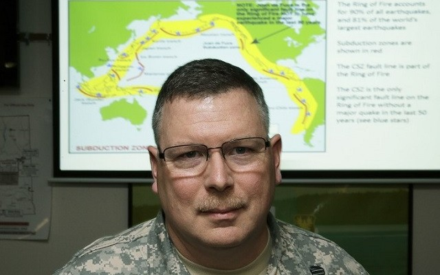 """Lt. Col. Clayton Braun, of the Washington State Army National Guard, poses for a photo, Wednesday, Jan. 20, 2016, at Camp Murray in Washington state in front of a slide showing earthquake-prone fault lines. Since 2013, Braun has led a team putting together a military response plan should an earthquake and tsunami happen in Washington state, as part of federal, state and military preparation for the """"Big One"""" along the Cascadia Subduction Zone. (AP Photo/Ted S. Warren)"""