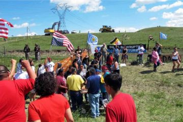 Native Americans protest the Dakota Access oil pipeline on Friday, Aug.  12, 2016 near the Standing Rock Sioux reservation in southern North Dakota. The Standing Rock Sioux Tribe went to court to try to block a $3.8 billion pipeline that's going in the ground fast to carry oil from North Dakota to Illinois. Now tribal members are trying to turn up the heat, with arrests in the pipeline construction zone near the 2.3-million acre reservation that straddles the North Dakota-South Dakota border. (AP Photo/James MacPherson).