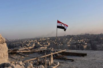 A Syrian national flag flutters near a general view of eastern Aleppo after Syrian government soldiers took control of al-Sakhour neigbourhood in Aleppo, Syria in this handout picture provided by SANA on November 28, 2016. SANA/Handout via REUTERS