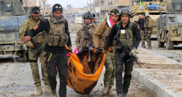 Iraqi government forces and members of Iraq's elite counter-terrorism service carry the body of a comrade during battles with Islamic State (IS) group jihadists as they try to secure all the neighbourhoods of Ramadi, the capital of Iraq's Anbar province, about 110 kilometers west of the capital Baghdad, on January 1, 2016.  Iraq declared the city of Ramadi liberated from the Islamic State group on December 28 and raised the national flag over its government complex after clinching a landmark victory against the jihadists. AFP PHOTO / STR / AFP / STR        (Photo credit should read STR/AFP/Getty Images)