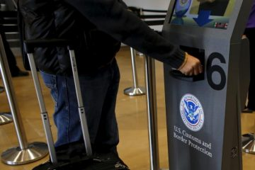 A traveler has his passport scanned as he passes through U.S. Customs and Immigration after using the Cross Border Xpress pedestrian bridge between San Diego and the Tijuana airport on the facility's opening day in Otay Mesa, California December 9, 2015. The privately run facility allows ticketed passengers to skip long border waits and clear U.S. Customs for a fee. REUTERS/Mike Blake  - RTX1XZ6I