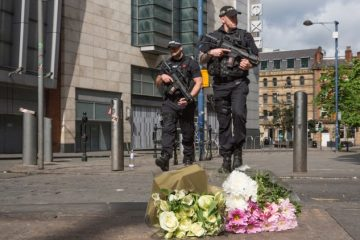 MANCHESTER, ENGLAND - MAY 23:  Armed police patrol on Shudehill walking past the first floral tributes to the victims of the terrorist attack on Shudehill, May 23, 2017 in Manchester, England. An explosion occurred at Manchester Arena as concert goers were leaving the venue after Ariana Grande had performed. Greater Manchester Police are treating the explosion as a terrorist attack and have confirmed 22 fatalities and 59 injured.  (Photo by Christopher Furlong/Getty Images)